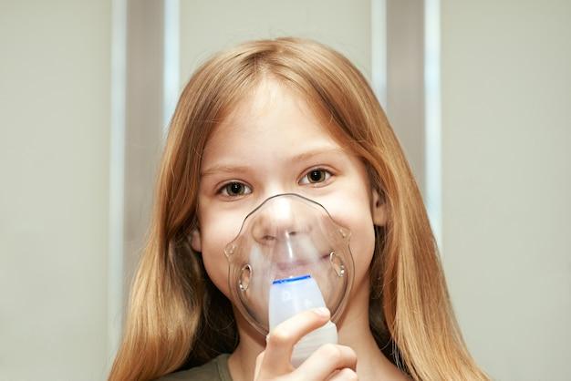 Niña usando un inhalador en interiores