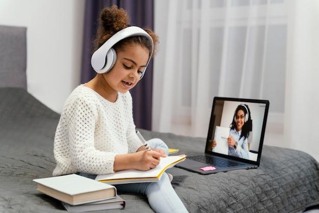 Niña usando laptop para escuela en línea