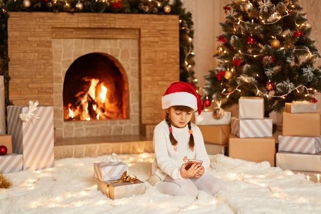 Niña usando un teléfono inteligente, revisando las redes sociales o jugando videojuegos, vestida con suéter blanco y sombrero de santa claus, posando en la sala festiva con chimenea y árbol de navidad.