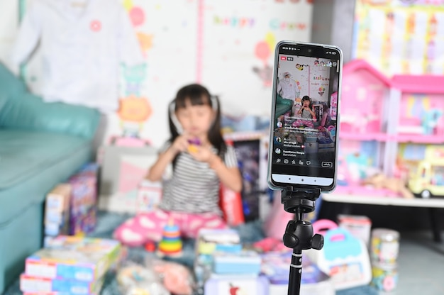 Niña vendiendo juguetes en línea mediante transmisión en vivo por teléfono inteligente, comercio electrónico en línea comercial en casa