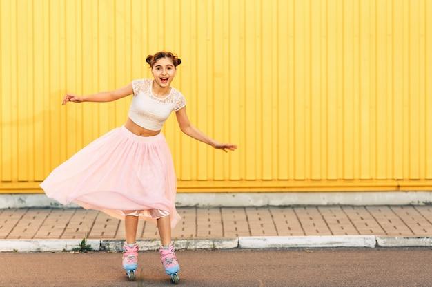 Niña en verano patinar sobre pared amarilla