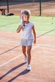 Niña vestida de blanco uniforme con raqueta de tenis en el hombro caminando en la cancha de tenis al aire libre al atardecer.