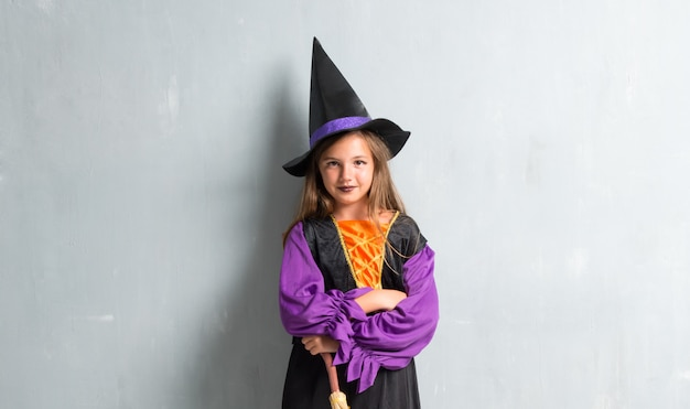 Niña vestida de bruja para las vacaciones de halloween con los brazos cruzados