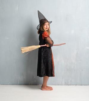 Niña vestida como una bruja y sosteniendo una escoba para las vacaciones de halloween con los brazos cruzados