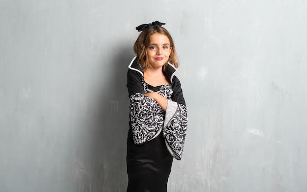 Niña vestida como un vampiro para las vacaciones de halloween con los brazos cruzados