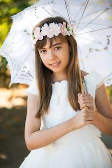 Niña vestida de comunión en el parque con un paraguas mirando a la cámara