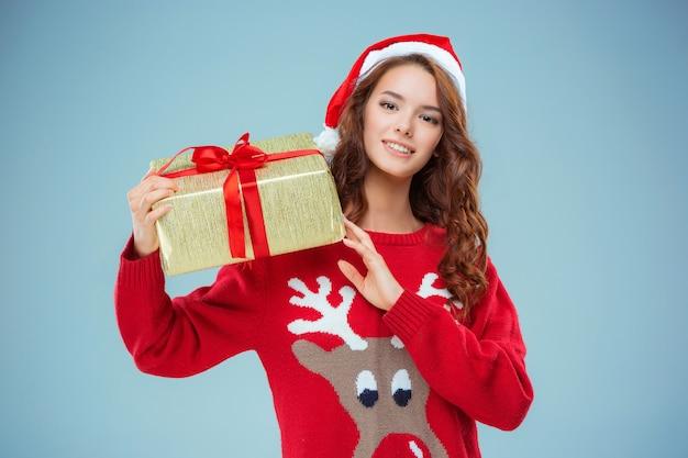 Niña vestida con gorro de papá noel con un regalo de navidad. ella está mirando a la cámara. concepto de vacaciones con fondo azul.