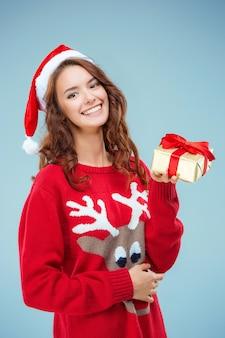 Niña vestida con gorro de papá noel con un regalo de navidad