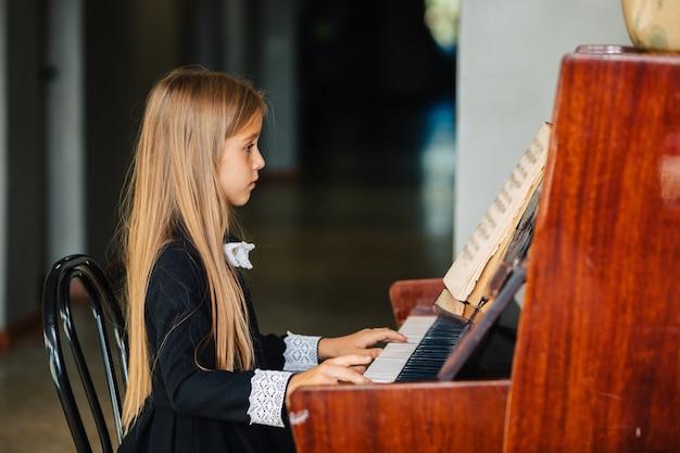 Niña vestida de negro aprende a tocar el piano. el niño toca un instrumento musical.