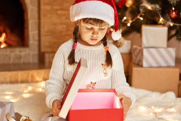 Niña vestida con suéter blanco y sombrero de santa claus, abriendo la caja actual con algo brillante en el interior, posando en la sala festiva con chimenea y árbol de navidad.