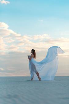 Una niña en un vestido blanco mosca baila y posa en el desierto de arena al atardecer
