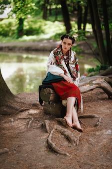 Niña en un vestido bordado ucraniano sentado en un banco cerca del lago