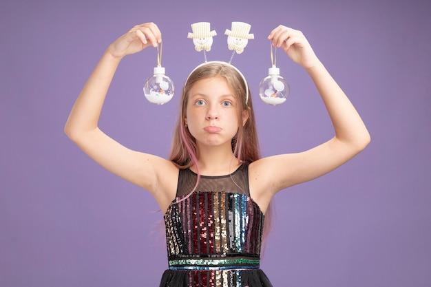 Niña en vestido de fiesta brillante y diadema divertida sosteniendo bolas de navidad mirando a cámara con cara seria sobre fondo púrpura