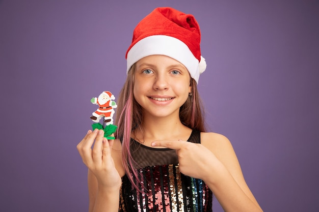 Niña en vestido de fiesta de brillo y gorro de papá noel que muestra el juguete de navidad apuntando con el dedo índice sonriendo de pie sobre fondo púrpura