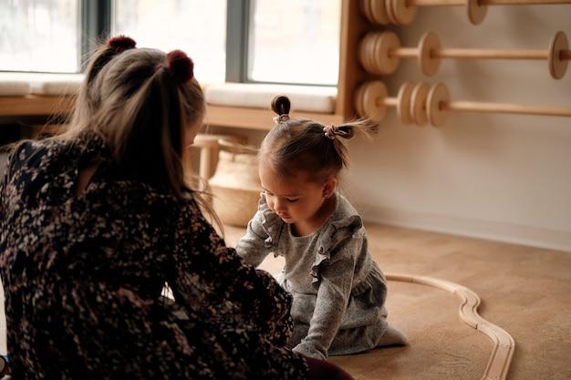 Niña con un vestido gris juega en la habitación de los niños con un ferrocarril de madera y un tren que es