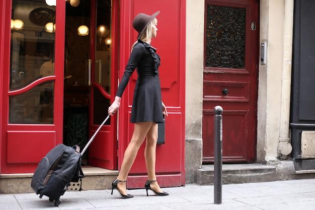 Una niña con un vestido negro corto con un sombrero y una maleta está caminando por la calle en parís