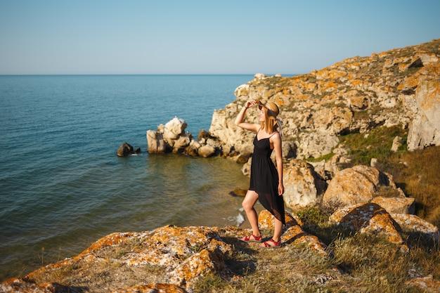 La niña en un vestido negro y sombrero en una playa rocosa mira al mar
