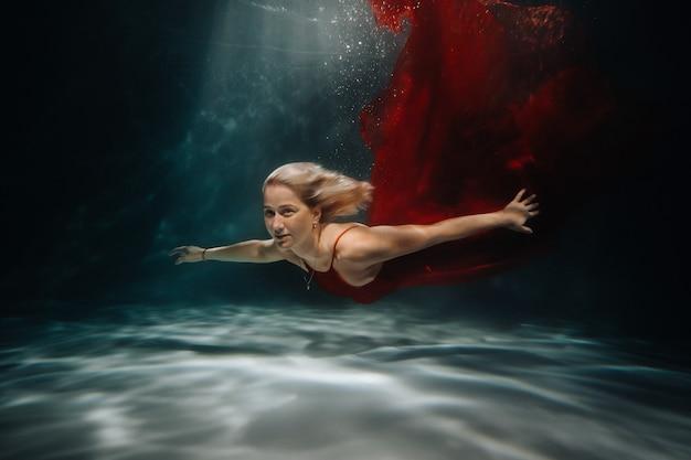 Una niña con un vestido rojo está nadando bajo el agua.