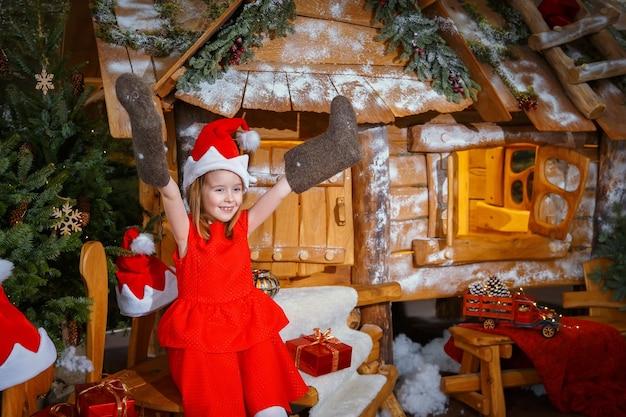Niña con un vestido rojo con un regalo de navidad y botas de fieltro cerca de una casa fabulosa