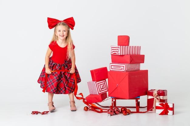 Niña con un vestido rojo rueda un trineo con regalos para el año nuevo. fondo blanco, espacio para texto. el concepto de navidad