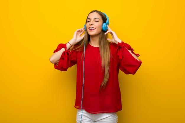 Niña con vestido rojo sobre pared amarilla escuchando música con auriculares