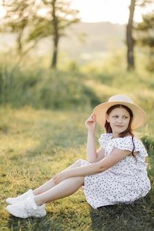 Una niña con un vestido y un sombrero se encuentra en el campo.
