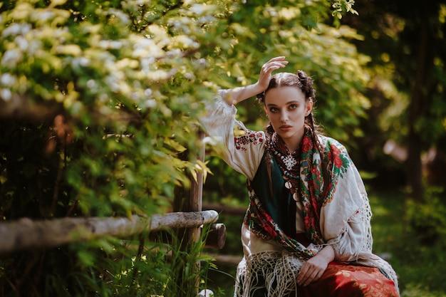 Niña con un vestido tradicional ucraniano está sentado en un banco en el parque