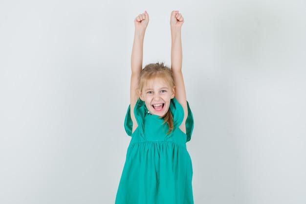 Niña en vestido verde levantando los brazos y gritando y mirando feliz