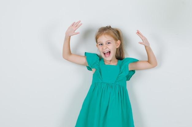 Niña en vestido verde levantando las manos y gritando y mirando enérgico