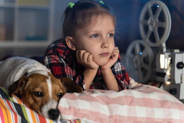 Niña viendo una película antigua en un proyector de películas vintage retro con un perro jack russell terrier en casa