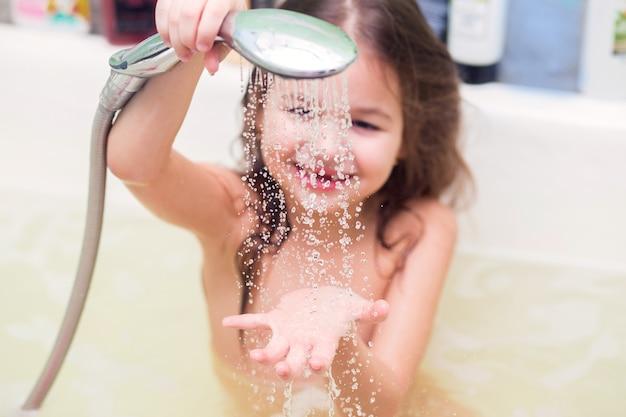La niña se vierte sobre el agua de una ducha, sentada en el baño. centrarse en gotas