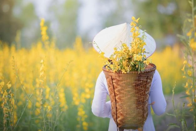 Niña vietnamita con flores amarillas.