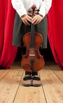 Niña con violín en el teatro del escenario