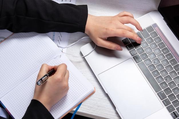 Una niña de la vista frontal tomando notas escribiendo notas en frente de la mesa con horarios y gráficos y usando la actividad comercial del trabajo portátil