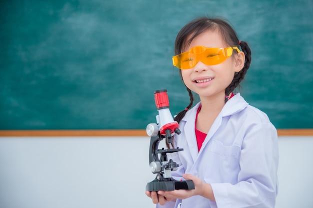 Niña vistiendo abrigo y sosteniendo microscopio