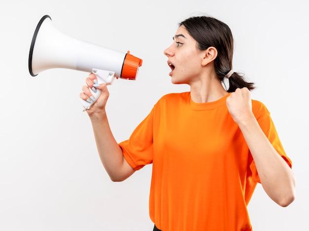 Niña vistiendo camiseta naranja gritando al megáfono apretando el puño emocional y excietd de pie sobre la pared blanca