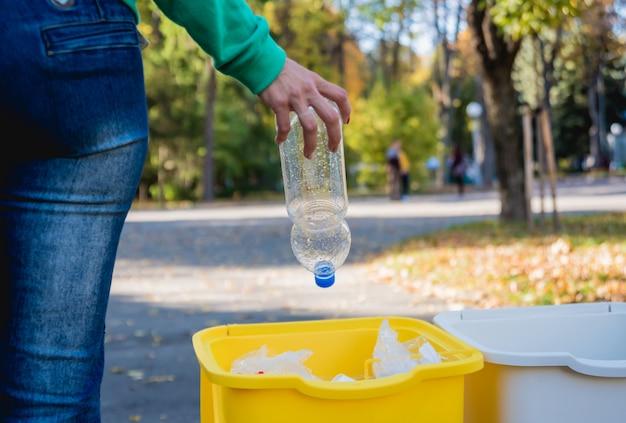 La niña voluntaria clasifica la basura en la calle del parque. concepto de reciclaje.