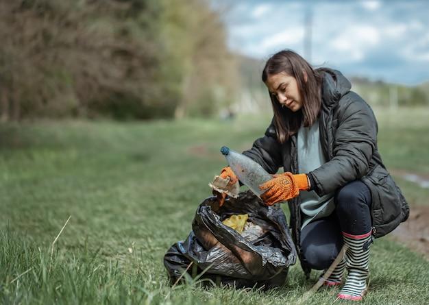 Niña voluntaria recoge basura en el bosque, cuida el medio ambiente.