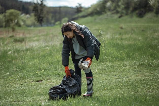 Niña voluntaria recolecta basura en el bosque, cuida el medio ambiente