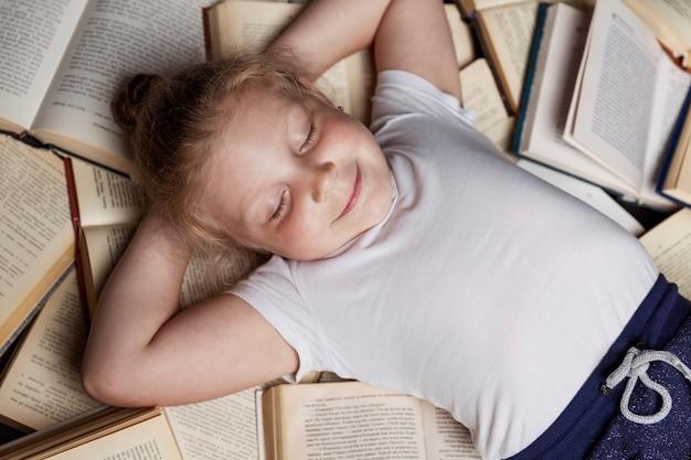 Niña yace sobre una pila de libros y duerme. educación y entrenamiento.