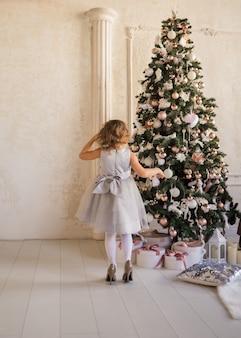 Una niña con los zapatos de su madre está de espaldas al árbol de navidad