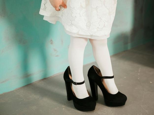Niña en zapatos de tacones negros de gran tamaño y vestido blanco cerca de la pared neo mint con espacio para texto, primer plano en las piernas
