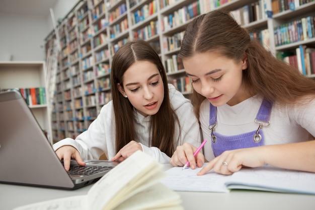 Niñas adolescentes, estudiar, juntos, en la biblioteca