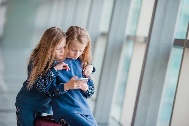 Niñas adorables en el aeropuerto esperando abordar y jugar con la computadora portátil
