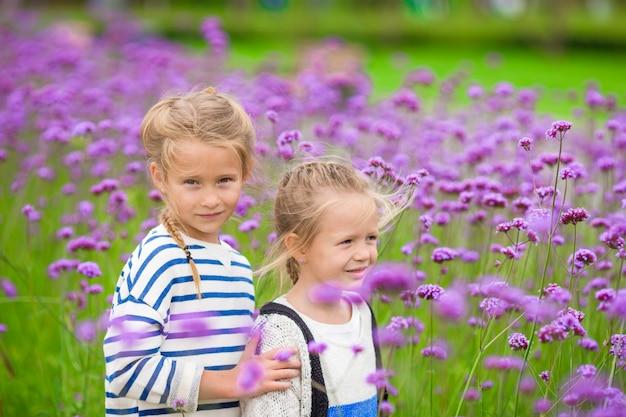 Niñas adorables caminando al aire libre en campo de flores
