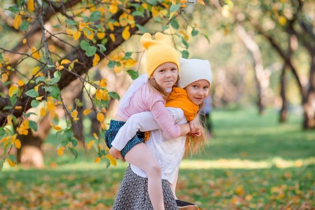 Niñas adorables en un día cálido en otoño parque al aire libre