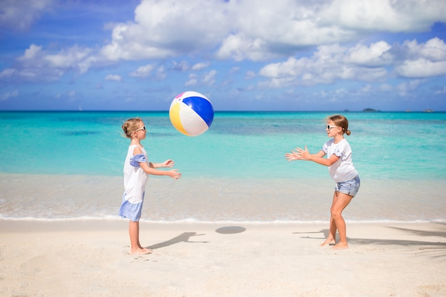 Niñas adorables jugando con la pelota en la playa