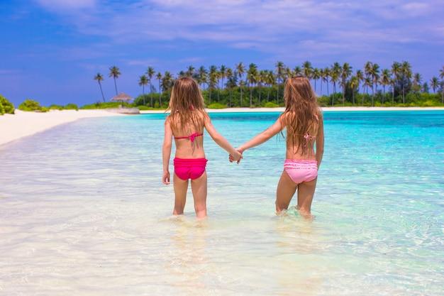 Niñas adorables en la playa durante las vacaciones de verano