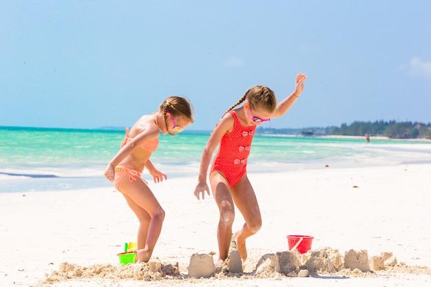 Niñas adorables durante las vacaciones de verano. niños jugando con juguetes de playa en la playa blanca