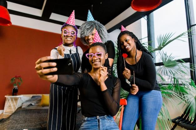 Niñas africanas felices celebran cumpleaños con sombreros y toman fotos en un teléfono inteligente